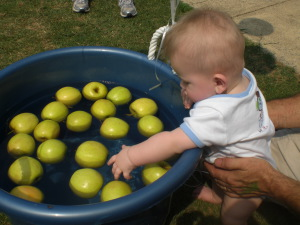 Un bambino cerca di prendere una mela con la mano sinistra
